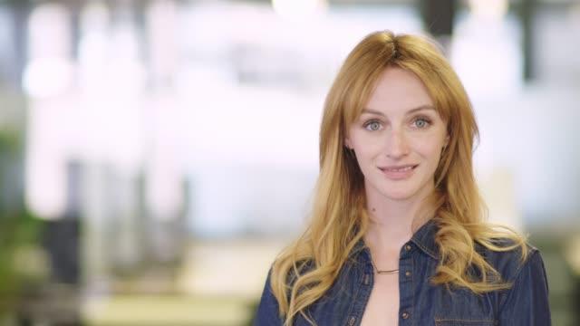 confident businesswoman smiling in office - 30 34 anni video stock e b–roll