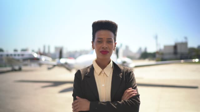 Confident businesswoman standing in airport hangar with arms crossed