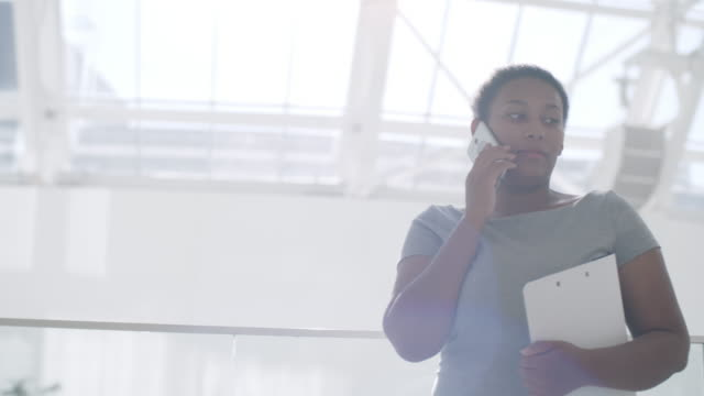 confident businesswoman talking on phone in office center - call center стоковые видео и кадры b-roll