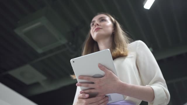 confident businesswoman with a digital tablet walking in the office - potere femminile video stock e b–roll