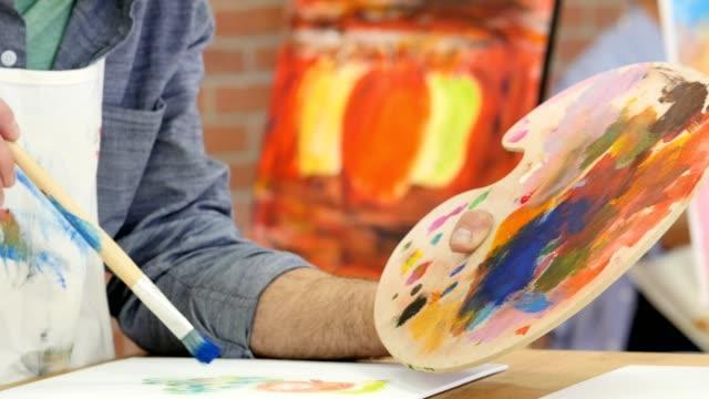 Confident Caucasian male artist paints in art studio video