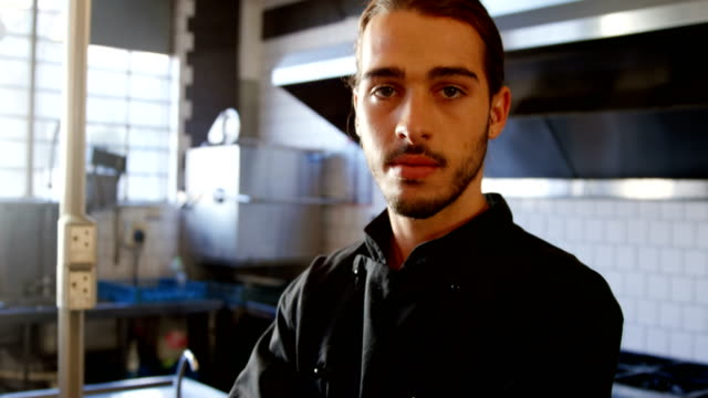 Confident chef standing in the commercial kitchen 4K 4k video