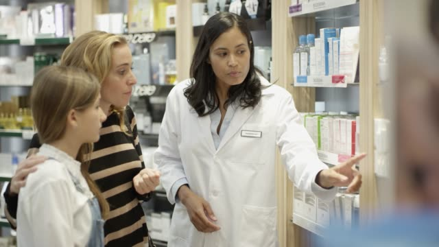 Confident chemist explaining medicines to customers Lockdown shot of confident chemist explaining female customers. Mother and daughter looking at medicines on shelf. They are standing in pharmacy. pharmacist stock videos & royalty-free footage