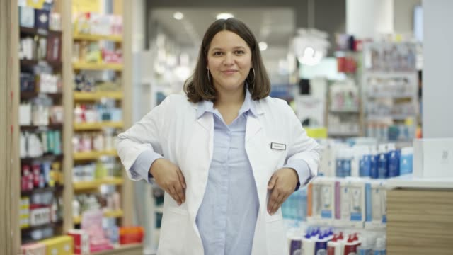 Confident chemist with hands in pockets in store Slow motion shot of confident pharmacist with hands in pockets. Female chemist wearing lab coat. She is standing in drug store. pharmacist stock videos & royalty-free footage