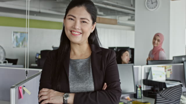 Confident Chinese businesswoman standing at desk in office - video