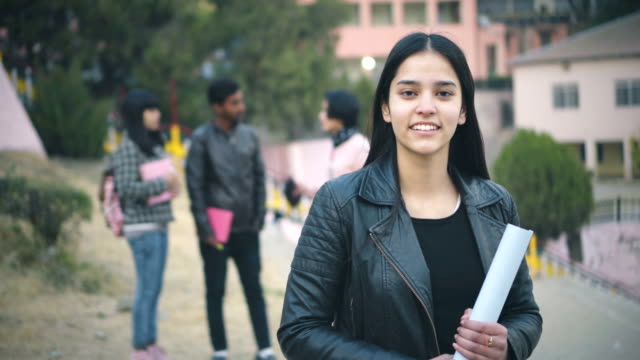 Confident college student looking at camera with toothy smile. Outdoor 4k video of happy, confident, Asian, Indian young adult female college student in college campus. She is looking at camera with toothy smile and holding rolled chart paper. Other students are standing in the background together in group. Shoot location Thodo Ground, Solan, (a city in mountain) Himachal Pradesh, India. indian subcontinent ethnicity stock videos & royalty-free footage