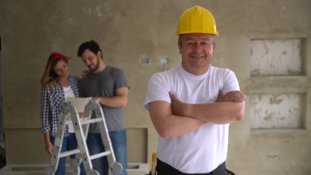 confident contractor at a home improvement project smiling at camera while couple are talking at background - imprenditore edile video stock e b–roll