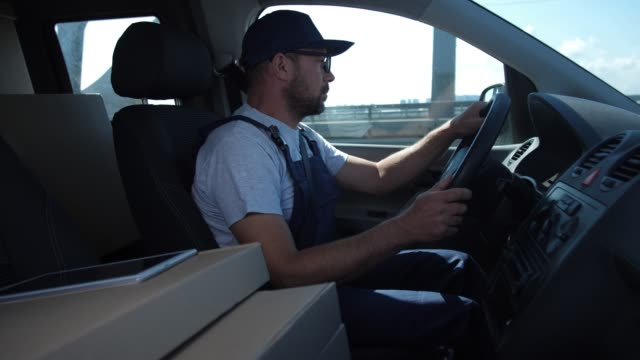 Confident delivery man driving car around city Bearded worker of delivery service in uniform confidently driving car along city road in hurry to client. Adult delivery man in cap and glasses driving over bridge while delivering order to customer vehicle part stock videos & royalty-free footage