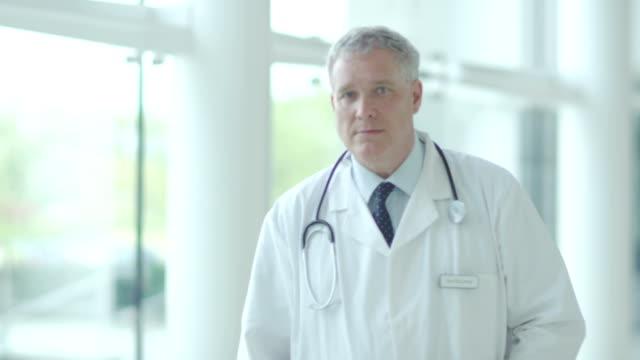 Confident doctor smiles into camera video
