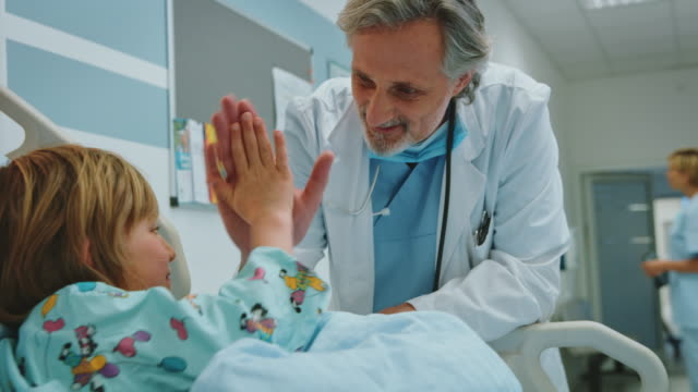 Confident doctor visiting boy in emergency room
