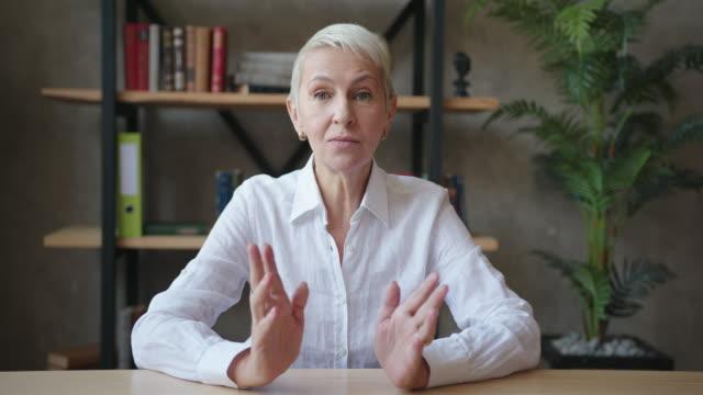 säker äldre kvinna lärare i vit skjorta gör videosamtal, online prata med webbkamera i klassrummet - huvudbild bildbanksvideor och videomaterial från bakom kulisserna