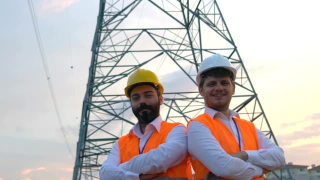 confident electrical engineers - sottostazione elettrica video stock e b–roll