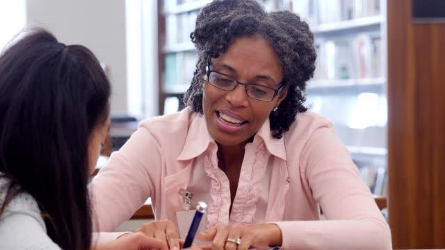 Confident elementary school teacher tutors schoolgirl after school