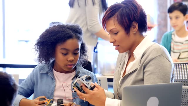 Confident elementary student build robot with teacher