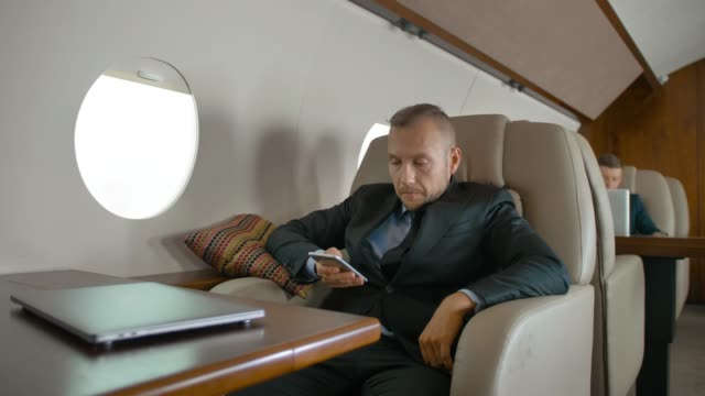 imprenditore fiducioso che viaggia sul suo jet privato e chiacchiera al cellulare - owner laptop smartphone video stock e b–roll
