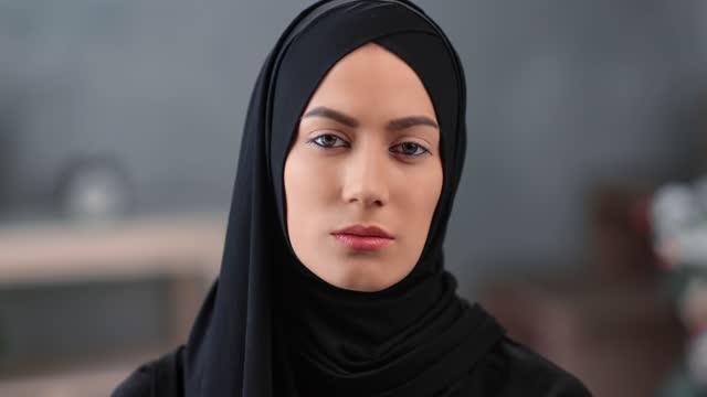 vídeos de stock e filmes b-roll de confident face of young saudi woman wearing black hijab headscarf. close up shot on 4k red camera - castanho