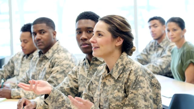 Confident female army cadet talks with unrecognizable professor Young Hispanic female army cadet gestures while discussing something with unrecognizable professor or officer. The professor is not shown in the video. The cadet gestures while making a point in her discussing with the professor. Her soldier classmates are sitting all around her. camouflage clothing stock videos & royalty-free footage