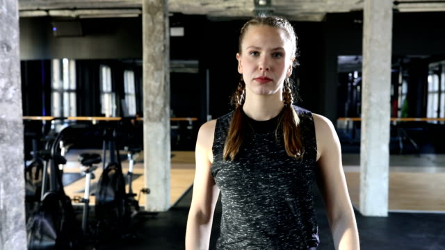 Confident female athlete walking in gym video