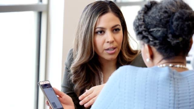 vidéos et rushes de l'employé de banque féminin confiant explique la banque mobile au client - expliquer