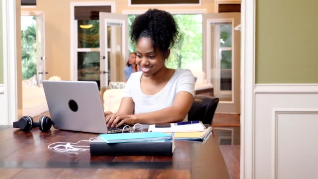 Confident female college student works on assignment at home Female college student smiles as she looks at her smartphone while using a laptop. She is working on an assignment. Her mother is using a smartphone in the background. student stock videos & royalty-free footage
