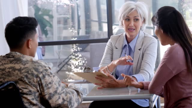 Confident female counselor gives advice to military soldier in wheelchair