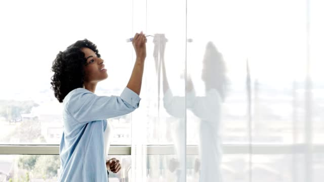 vídeos de stock e filmes b-roll de confident female creative professional jots ideas down on whiteboard - cabelo preto