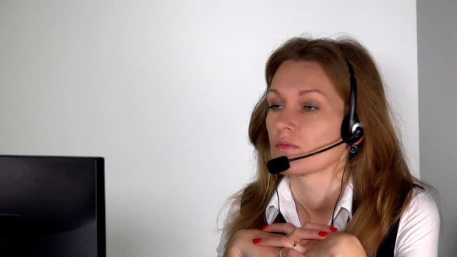 confident female customer service consultant with headset in front of computer video