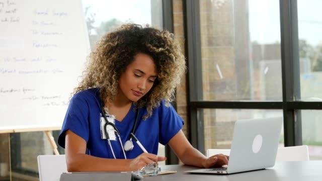 test sonuçlarını analiz etmek için dizüstü bilgisayar kendine güvenen kadın doktor kullanır - çekici insanlar stok videoları ve detay görüntü çekimi