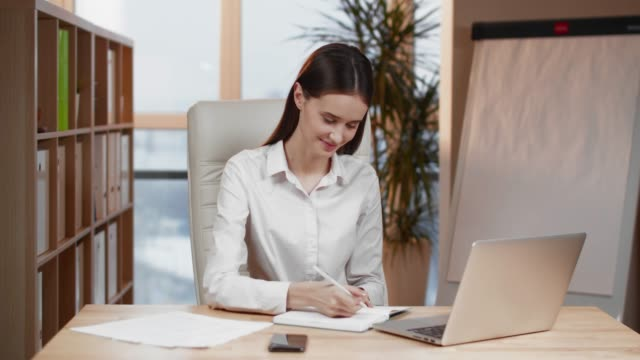 confident female entrepreneur planning her workday sitting at her desk holding pen thinking looking at notebook in office - treedeo stock videos and b-roll footage