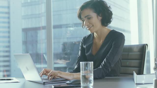 Ejecutivo mujer seguro trabaja en un portátil sentado en su escritorio en la oficina moderna con vistas a la gran ciudad. Sonriendo Busiesswoman exitosa utiliza la Laptop. - vídeo