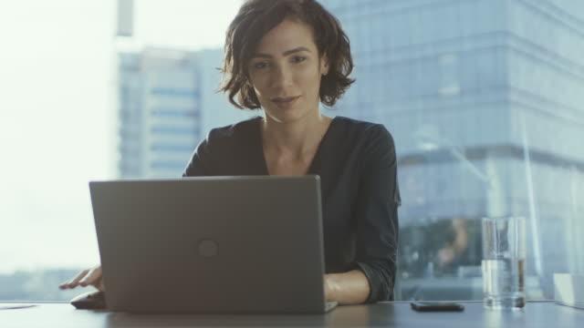 Ejecutivo mujer seguro trabaja en un portátil sentado en su escritorio en la oficina moderna con vistas al paisaje urbano arquitetonico. Busiesswoman portátil de usos. - vídeo