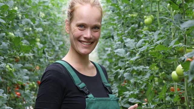 confident female farmer in greenhouse - bio food video stock e b–roll