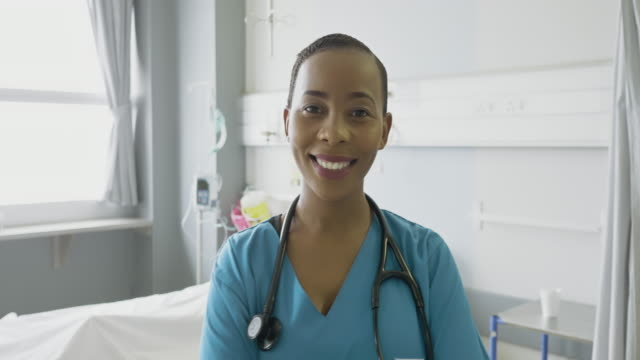 Confident female nurse standing in hospital Portrait of confident female nurse standing in hospital ward. Healthcare worker is smiling, She is in uniform. focus on foreground stock videos & royalty-free footage