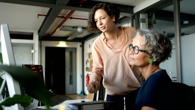 confident female programmers discussing at office - dorosły w średnim wieku filmów i materiałów b-roll