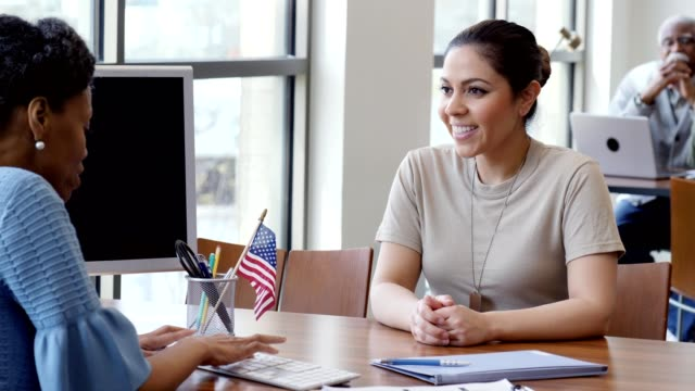 Confident female soldier talks with loan officer Smiling young adult female military soldier smiles and laughs as she talks with a female bank officer about a loan. The loan officer is finishing up inputting information on a desktop computer. The two women shake hands in agreement. military lifestyle stock videos & royalty-free footage