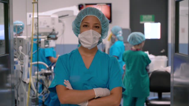 confident female surgeon wearing a protective mask while facing camera and crossing arms at a surgery room - face mask stock videos & royalty-free footage