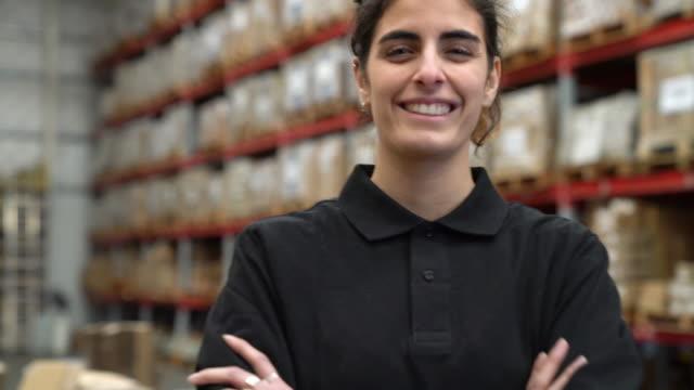vidéos et rushes de travailleuse confiant, souriant dans l'entrepôt - uniforme