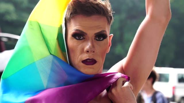zuversichtlich gay boy mit regenbogenfahne - gay man stock-videos und b-roll-filmmaterial