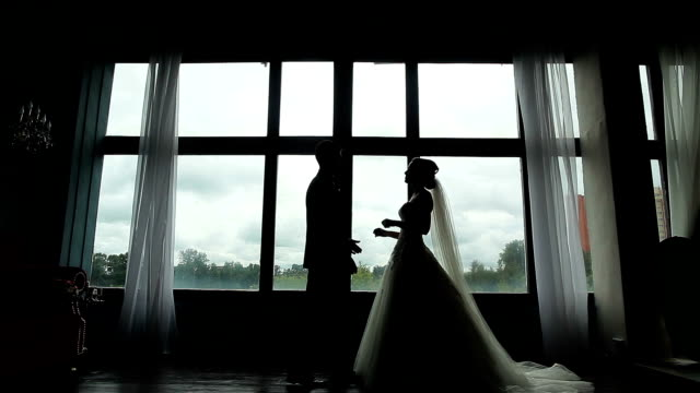 Confident groom meets happy bride first time seeing her in wedding dress silhouetted near window. Marrying couple embrace and kiss standing near huge window in room video