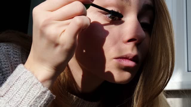 Confident happy young woman holding mascara apply on eyeleashes prepare getting ready in the morning. Woman doing makeup. Get ready for a date Confident happy young woman holding mascara apply on eyeleashes prepare getting ready in the morning. Woman doing makeup. Get ready for a date. Morning sunlight. mascara stock videos & royalty-free footage