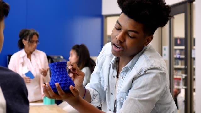 vídeos y material grabado en eventos de stock de tutor de secundaria seguro utiliza ayudas visuales durante la sesión de tutoría con alumnos de secundaria - escuela media