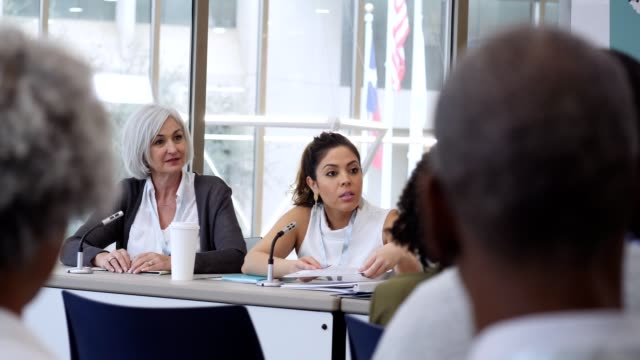 Confident Hispanic businesswoman listens to a question while participating in a panel discussion