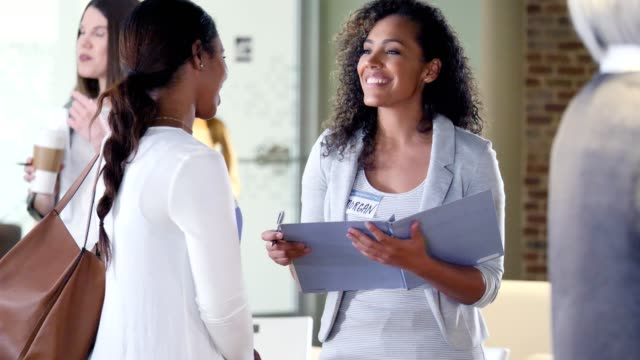 Confident homeowner association representative talks with young woman Cheerful mid adult African American female homeowner association representative takes notes while asking a young woman questions about their neighborhood. survey stock videos & royalty-free footage