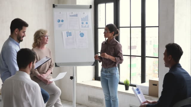 Confident indian coach training diverse employees give flip chart presentation