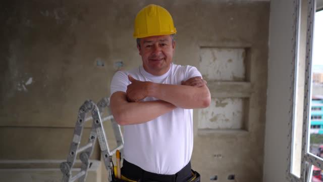 fiducioso operaio edile adulto latinoamericano in un appartamento sorridente alla telecamera che incrocia le braccia - artigiano video stock e b–roll