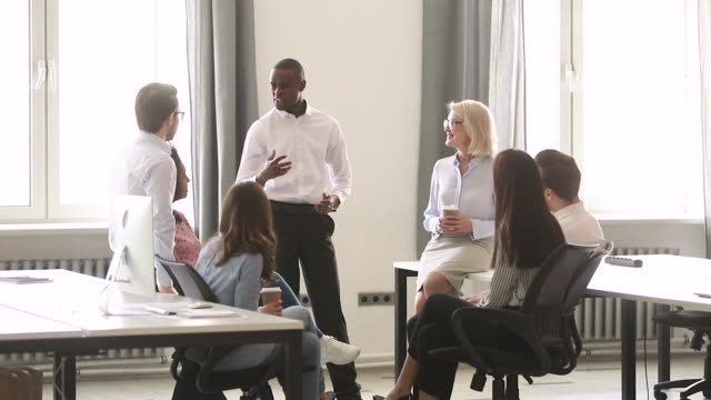 vídeos de stock, filmes e b-roll de ônibus africano masculino confiável do líder que motiva empregados da equipe na reunião - rh