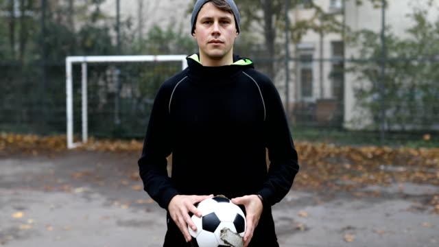 confident male athlete holding soccer ball - sportowiec filmów i materiałów b-roll