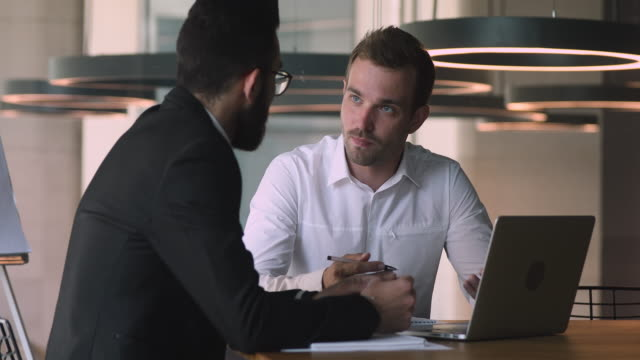 Confident male caucasian financial consultant talking to arabic client