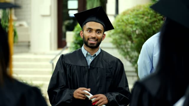 Confident male college graduate gives motivating speech to graduate