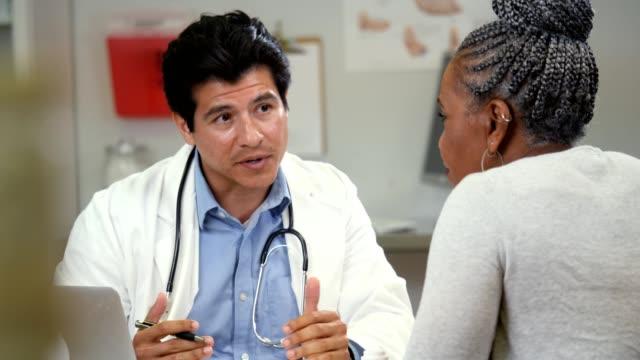 självsäker manliga läkare diskuterar testresultaten med ledande kvinnlig patient - patient bildbanksvideor och videomaterial från bakom kulisserna